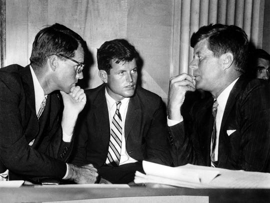 Robert F. Kennedy, left, confers with his brothers