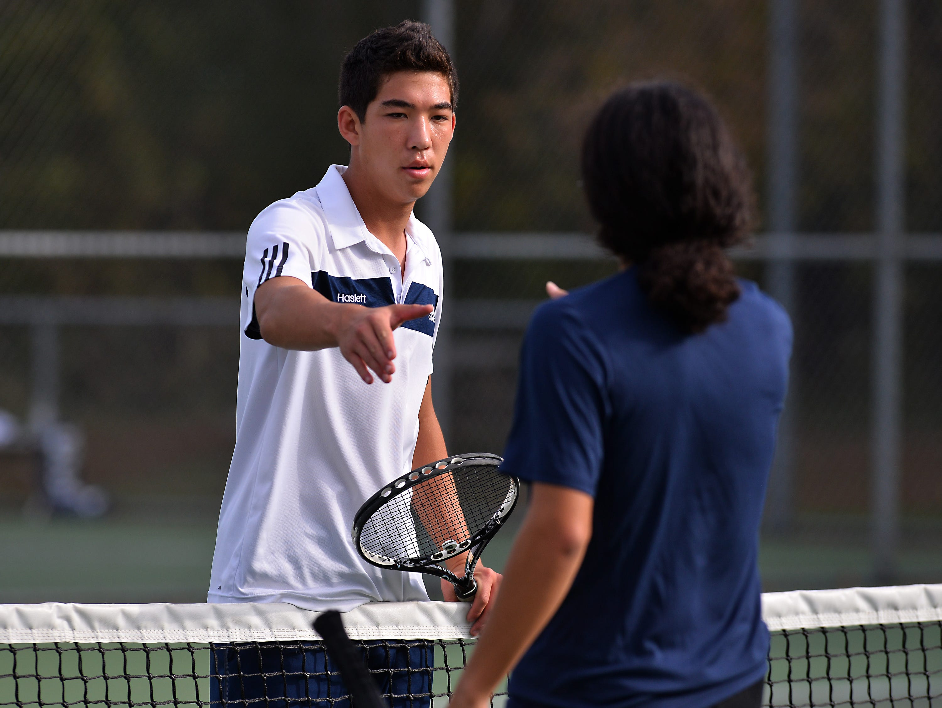 Haslett's Nate Choi left, and Eastern's Jonathan Hudy-Velasco, right, shake hands at the net Thursday 10/8/2015 after Choi won their match in early action of tennis regionals.