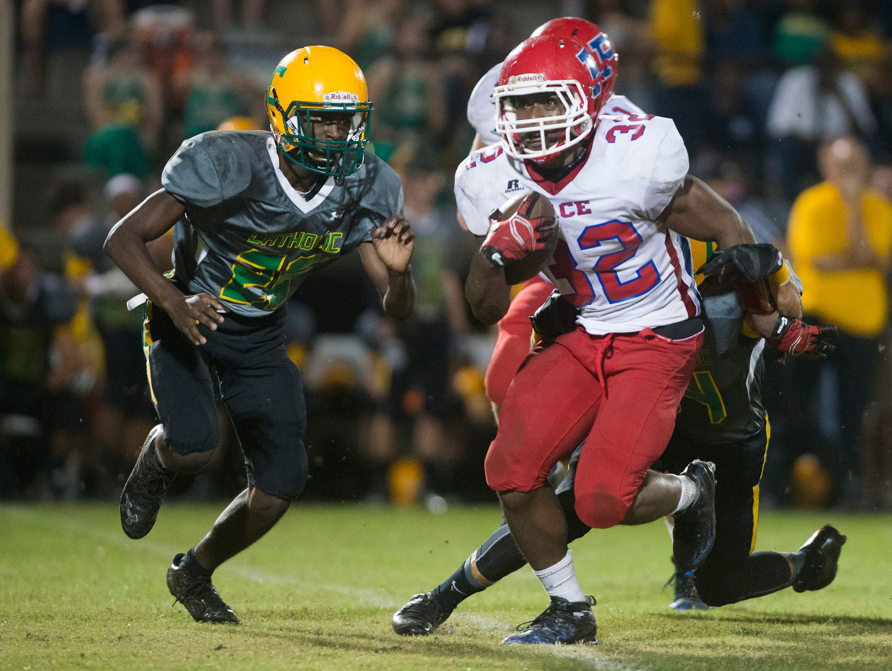 Pace High's running back, Anthony Johnson, (No. 32) gets wrapped up by Catholic High's Evan Junot, (No. 24) as Bryan Wright, (No. 26) comes in to strip the ball from Johnson during Friday night's final regular season prep football game.