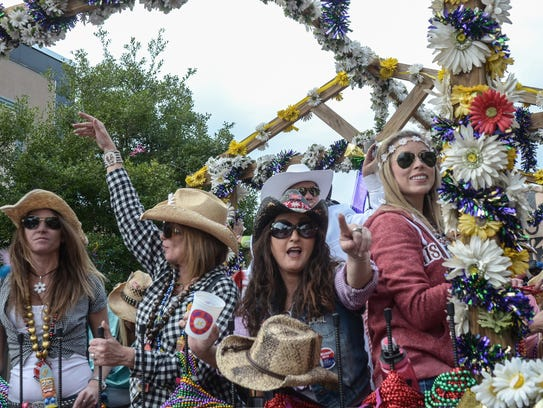 Members of the Krewe of Daisy Dukes throw beads to