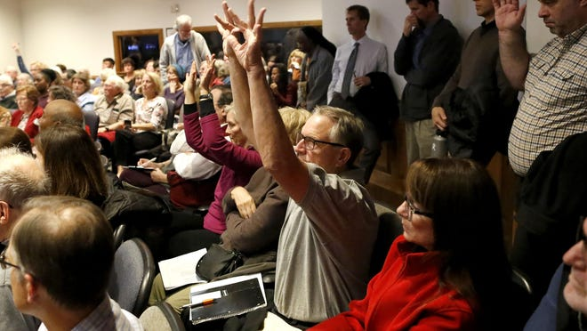 Citizens wave their hands to show their support for comments of disapproval of the GNV Rise affordable housing proposal during a City Commission meeting at City Hall in 2018.
