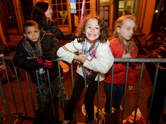 Revelers enjoy the Krewe of Lafitte Illuminated Mardi Gras Parade on Friday night as beads and moon pies are thrown along the parade route in downtown Pensacola.
