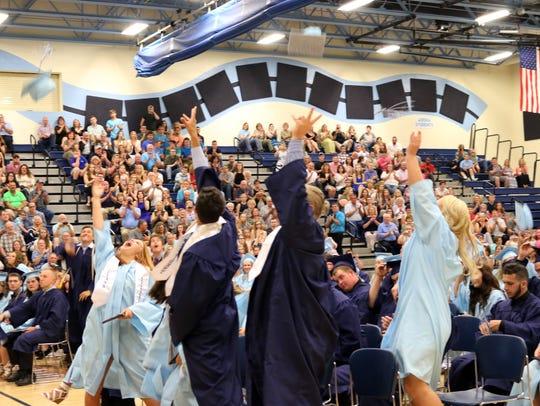 Adena High School graduates toss their caps after graduating