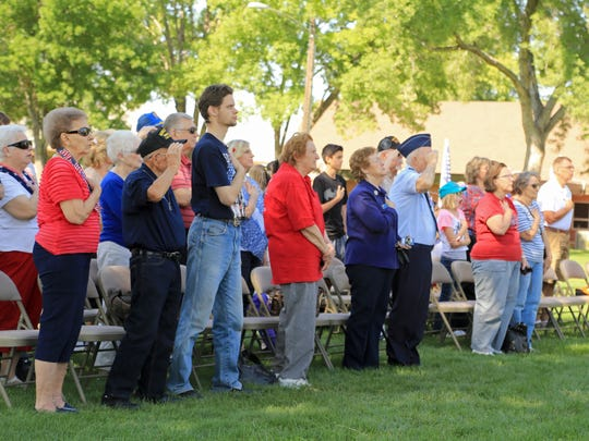 The audience salutes the flag during a Memorial Day service on Monday at Veterans Park in Washington City.