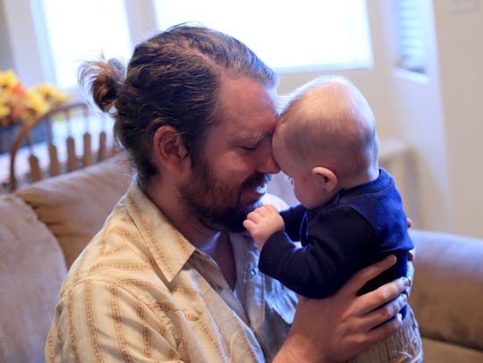 Jared Buhanan-Decker holds his 5-month-old son, JJ,