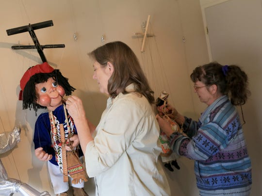 Sharon Evans and Lorie Hawley prepare marionettes for