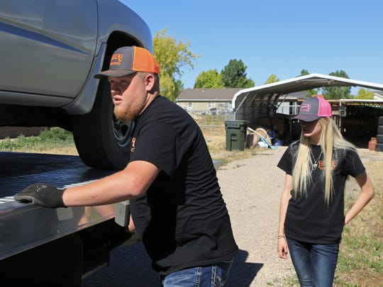 Laramy Brindley loads a pickup on a tow truck Wednesday in Enoch with the help of his sister, Jessi, as they work for their father's business, Ladd's Towing.