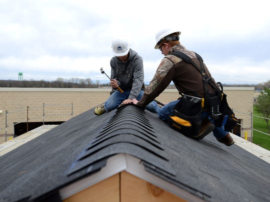 Daniel Ownby, left, a Canal Winchester High School student, and Brody Tonelotti, a Teays Valley High School student, shingle the roof of a mock house Tuesday at the Fairfield Career Center in Carroll. Ownby and Tonelotti are students in the construction technology program at the school.