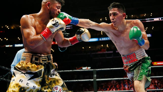 Leo Santa Cruz, right, lands a punch against Abner Mares during the seventh round of their fight Saturday. Santa Cruz won by majority decision (Photo: Danny Moloshok, AP)