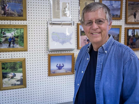 Bill Clock stands in his garage filled with photographs