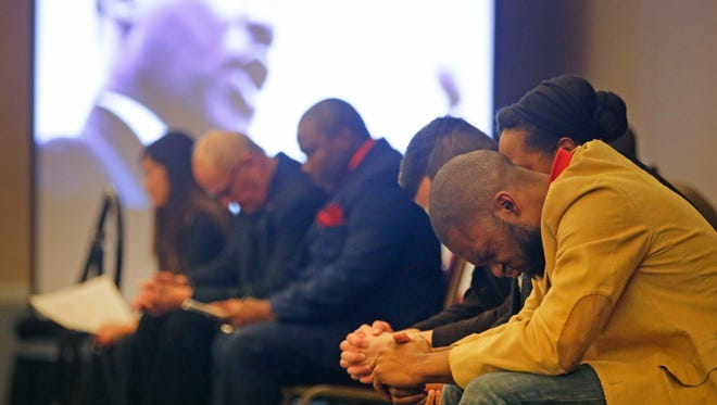 Speaker Emmanuel Christopher of Appleton bows his head in prayer along with others during a community worship service to mark the 50th anniversary of Dr. Martin Luther King's assassination Sunday at the Radisson Paper Valley Hotel in Appleton.