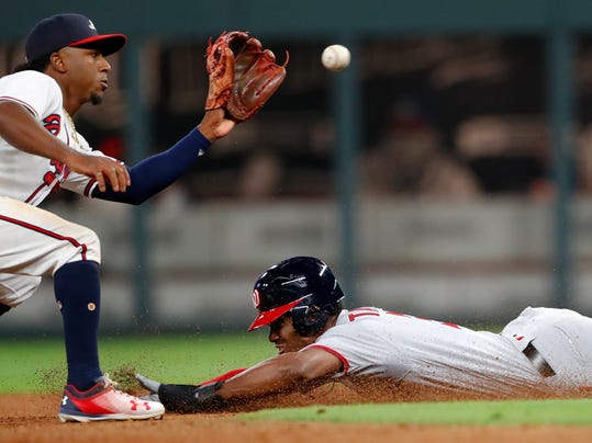 Washington Nationals' Michael A. Taylor (3) steals second base as Atlanta Braves second baseman Ozzie Albies (1) handles the late throw in the seventh inning of a baseball game Monday, April 2, 2018, in Atlanta. (AP Photo/John Bazemore)
