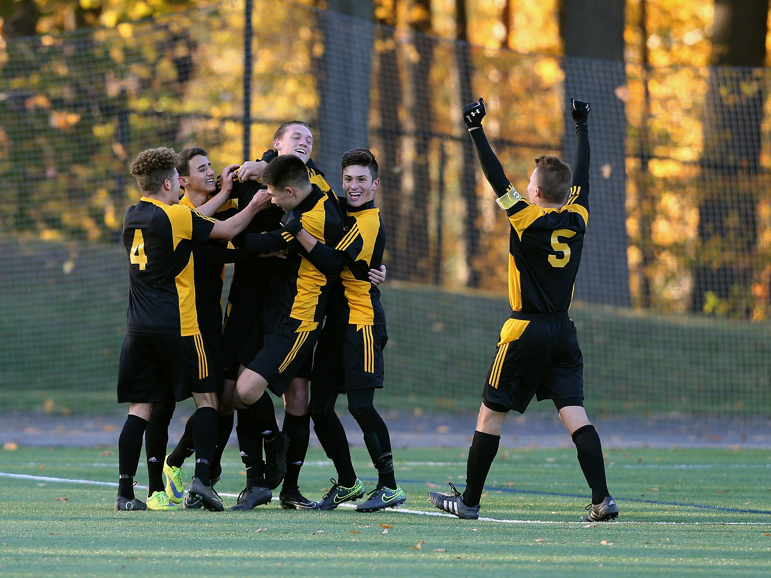 Greece Athena's Zach Koons (center) is mobbed by teammates after one of his two goals in the Class A1 final against Brockport. Athena went on to win 2-0.