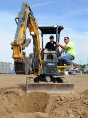 James Stoneburner works a piece of construction equipment with help from a trained operator Friday at Company Wrench.