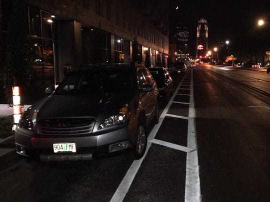 "Cars parked in the newly-painted protected bike lane on Aug. 25 as the ""Complete Streets"" design was in its construction phase on East Grand Avenue in Des Moines."