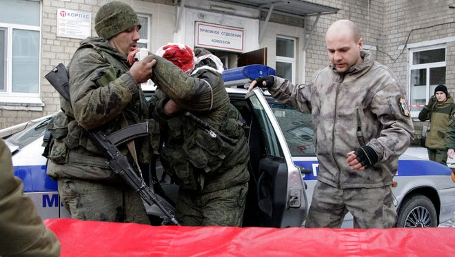 Separatist rebels help an injured comrade near a hospital in Donetsk, Ukraine, on Feb. 16, 2015.