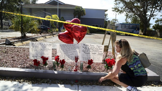 A woman sets up a makeshift memorial in memory of the senior citizens who died at the Rehabilitation Center at Hollywood Hills, Fla.
