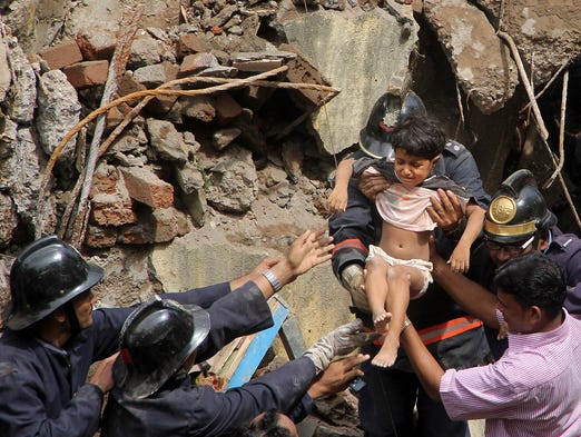 Firefighters rescue a girl from a collapsed building on Sept. 27 in Mumbai, India. Three people were killed when a multistory residential building suddenly collapsed.