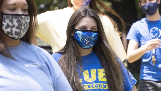A Southeastern Oklahoma State University student is shown wearing a school-branded face mask. The university reports that it experienced record enrollment this fall.