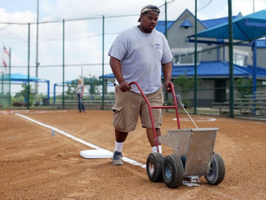 Nate Bailey of Murfreesboro Parks and Recreation lays down the third-base line on one of the softball fields as preparations are made for the TSSAA Spring Fling at StarPlex Park in May 2015.