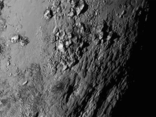 A region near Pluto's equator shows a range of mountains rising as high as 11,000 feet.