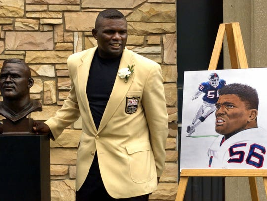 Lawrence Taylor poses with his portrait and bust during enshrinement ceremonies at the Pro Football Hall of Fame on Aug. 7, 1999 in Canton, Ohio.