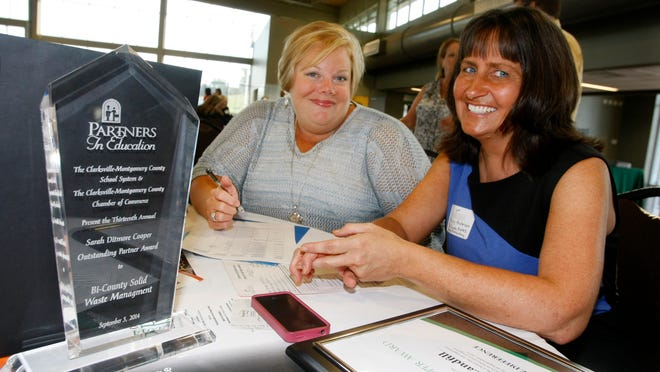 Principal Emily N. Vaughn, left, and Mary Anderson of Bi-County Solid Waste Management System visit after the the Bi-County received the Sarah Ditmore Cooper award Friday at the annual Partners in Education Breakfast.