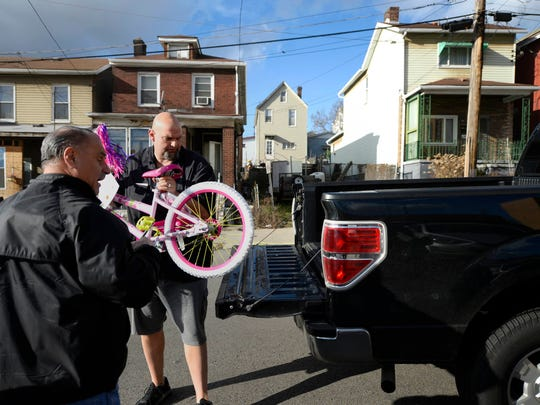 Braddock Police Chief Frank DeBartolo, left, brings a donated bike to Mayor John Fetterman to load in his truck in Braddock, Pa., Tuesday, December 22, 2015.