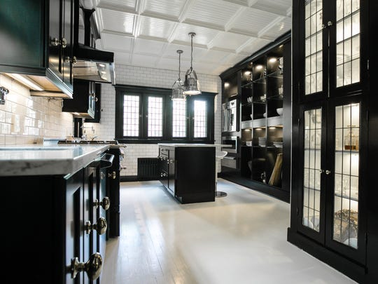 The striking kitchen has over-the-top appliances and white tile walls.  The nickel hanging lights were search lights from a large ship. All the leaded glass was added.
