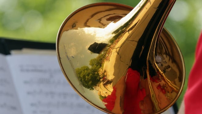The crowd is reflected in the bell of a trombone during the Memorial Day program at Fountain Park Monday May 30, 2016 in Sheboygan.