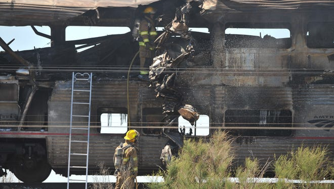 Firefighters douse the wreckage of an Amtrak passenger car on June 24, 2011.