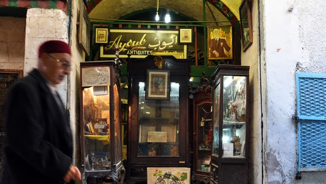 A man wearing a traditional Tunisian hat walks past an antique store in Tunis's old quarter.