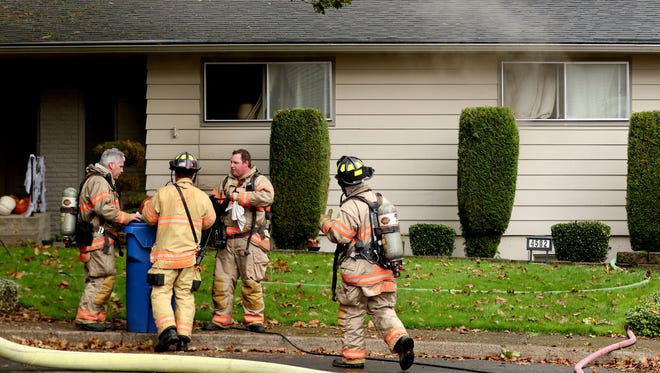 Smoke escapes from windows as Salem Fire Department personnel work to put out a residential fire in south Salem on Wednesday, Oct. 28, 2015.