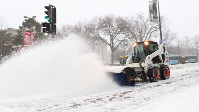 Snow gets cleared off the sidewalk along Clinton Street on Monday, Dec. 28, 2015.