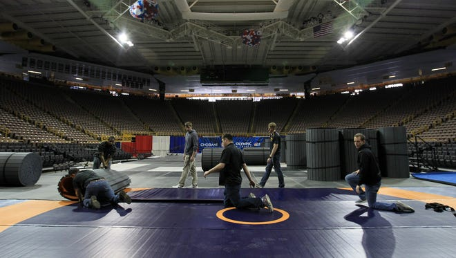 Wrestling mats are rolled out inside Carver-Hawkeye Arena in preparation for the U.S. Olympic Wrestling Team Trials on Wednesday, April 6, 2016.