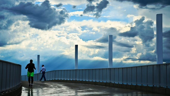 A jogger and walker make their way along the ramp of the Big Four Bridge Wednesday morning as clouds roll overhead.