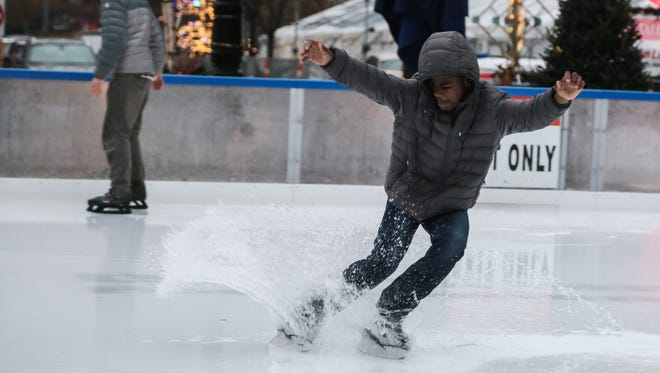Corey Jones, 15, of Detroit sprays water while stopping on his ice skates after rain water puddled on the rink at Campus Martius in downtown Detroit on Monday December 26, 2016.