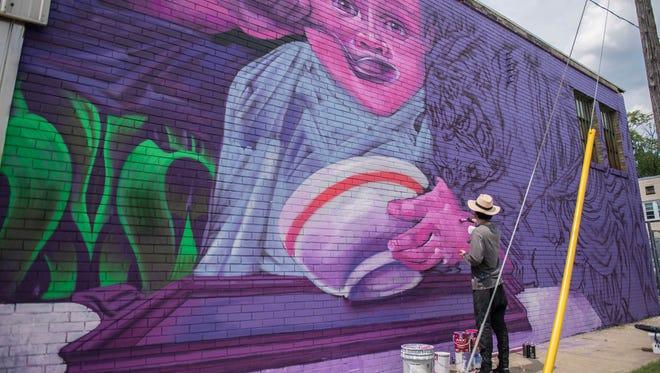 "Werc Alvarez from Brooklyn in New York works on a mural at 69 Calhoun St., near the Charitable Union, as part of the street art festival ""Color the Creek"" on Thursday."