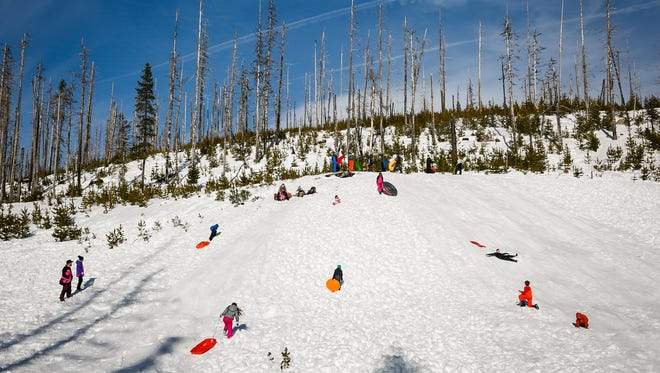 Sledders enjoy the snow on a warm day at Santiam Sno-Park on Sunday, Jan. 28, 2018. Basin-wide snowpack levels for the Cascades measured at about 51 percent of normal Sunday afternoon, according to the National Weather Service.