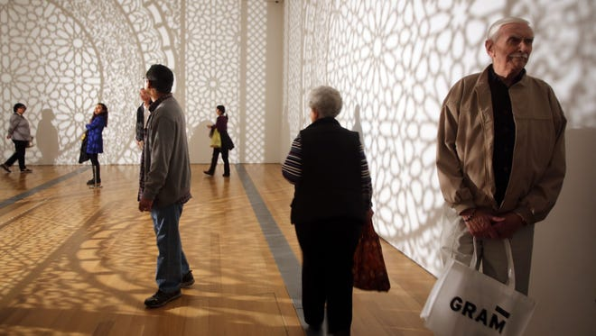 """People take in the 3-D piece of Anila Quayyum Agha's """"Intersections"""" at the Grand Rapids Art Museum Tuesday, Sept. 30, 2014, during ArtPrize 2014."""