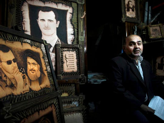FILE -- In this Feb. 24, 2016 file photo, a Syrian shopkeeper waits for customers next to paintings of of President Bashar Assad, and Hezbollah leader Sheikh Hassan Nasrallah, center, at the Souk Tawil market in Damascus, Syria. Turkey said Thursday, Dec. 29, 2016, that Lebanon's militant Hezbollah group, which has sent thousands of fighters to support President Bashar Assad, should withdraw from Syria. In an interview with Turkey's A Haber news channel, Foreign Minister Mevlut Cavusoglu also said Turkey and Russia are close to reaching an agreement on a nationwide Syrian cease-fire that would come into effect by the end of the year.