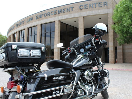 An Abilene Police Department motorcycle is parked outside