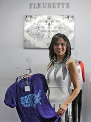 Ghada Bawadi shows off clothing inside her Fleurette retail shop offering men's and women's activewear in the Plankview Green Shopping Center in Sheboygan Falls. The store opens Dec. 1.