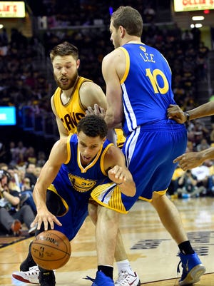 Golden State Warriors guard Stephen Curry (30) drives to the basket against Cleveland Cavaliers guard Matthew Dellavedova (8) around the pick of Golden State Warriors forward David Lee (10) during the first quarter in game four of the NBA Finals at Quicken Loans Arena.