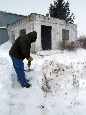 Bob Manzke shovels his way to feed the cats in the midst of the spring storm that hit the state last weekend.