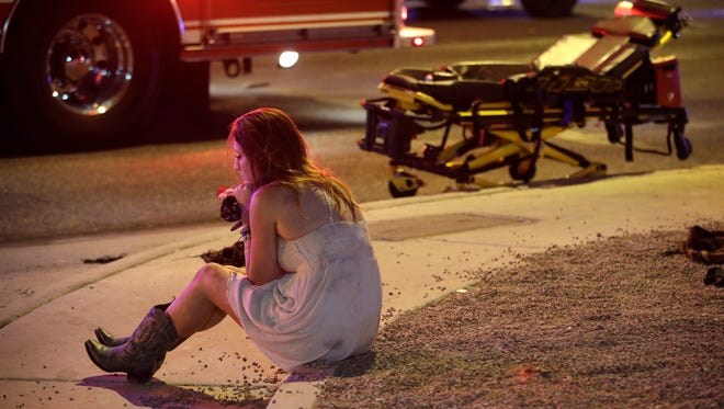 A woman sits on a curb at the scene of a shooting outside of a music festival along the Las Vegas Strip, Oct. 2, 2017.