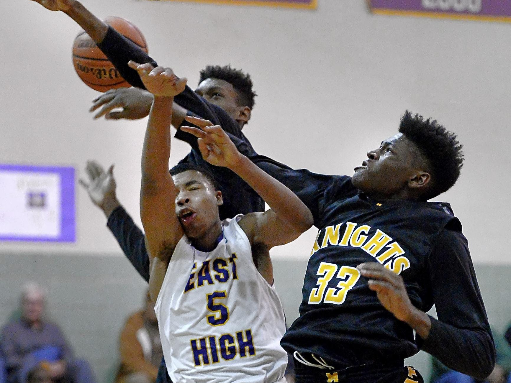 McQuaid's Isaiah Stewart, right, and Thomas Jones, back, stuff a shot attempt by East's Theodore Buckner during a regular season RCAC game played at East High School on Tuesday. McQuaid beat East 80-73.