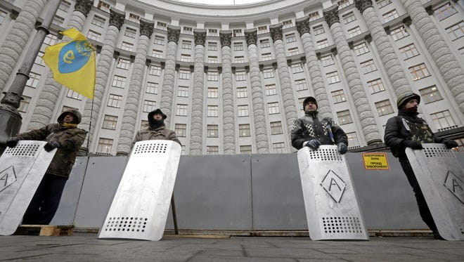 Protesters guard the Ukrainian Government building in downtown Kiev  on Tuesday.