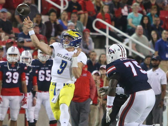 Delaware quarterback J. P. Caruso eludes pressure, including from Stony Brook's Sam Kamara (right) and throws a 23-yard touchdown pass in the first quarter at LaValle Stadium Saturday.