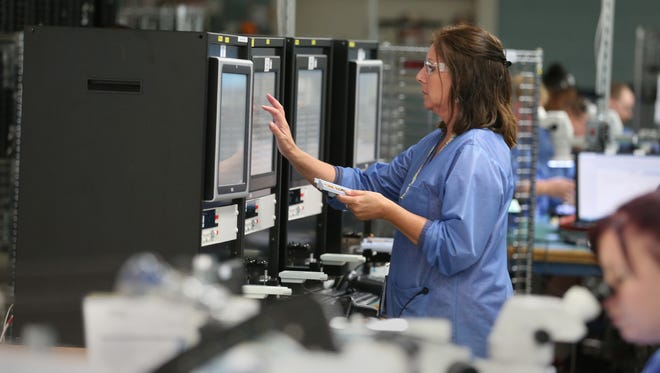 A worker runs an inspection area to test devices made at IEC Electronics Corp. in Newark, Wayne County.